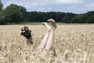 Naked legs of girl and hand holding bunch of flowers in a field - PSTF00249