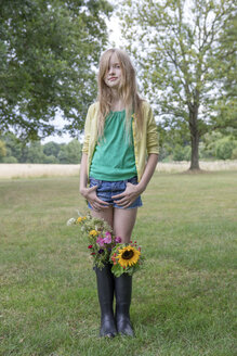 Portrait of blond girl standing on a meadow with bunches of flowers in her rubber boots - PSTF00252