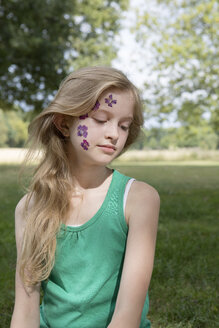 Portrait of blond girl with tattoo of pressed flowers on her face - PSTF00258