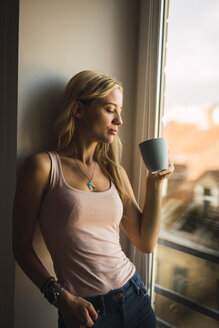 Blond young woman holding coffee mug at the window - KKAF01981