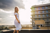 Blond young woman standing on roof terrace at sunset wearing white dress - KKAF02008