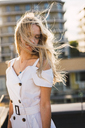 Blond young woman with windswept hair wearing white dress outdoors - KKAF02011
