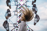 Long-haired young woman shaking her hair on a funfair - KKAF02014