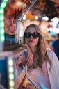 Portrait of young woman wearing sunglasses on a funfair - KKAF02017