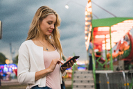 Young woman using cell phone on a funfair - KKAF02023