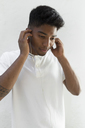 Portrait of young man listening music with earphones - JPTF00002