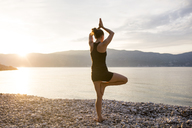 Young woman doing yoga on a stony beach at sunset, tree position - JESF00178