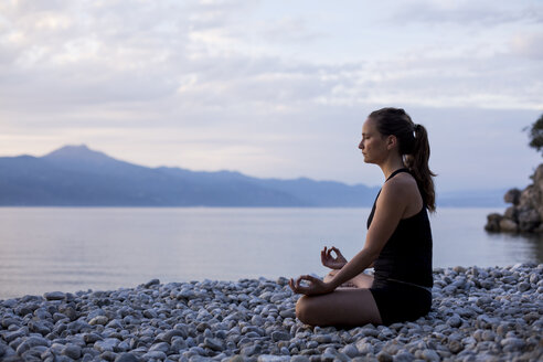 Young woman doing yoga at the stony beach in the evening, meditation - JESF00181