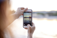 Close-up of woman taking cell phone picture of tbe sea at sunset - PSIF00105