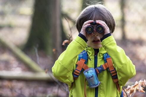 Boy looking through binoculars in forest - AURF06064