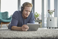 Young man lying on carpet at home wearing headphones and using tablet - RBF06828