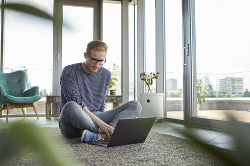 Young man sitting on carpet at home using laptop - RBF06846