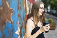 Young woman holding cup of coffee, standing in front of metal fence with stars and stripes - GIOF04502