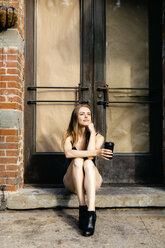 Young woman sitting in the street on a doorstep, holding a cup of coffee - GIOF04526
