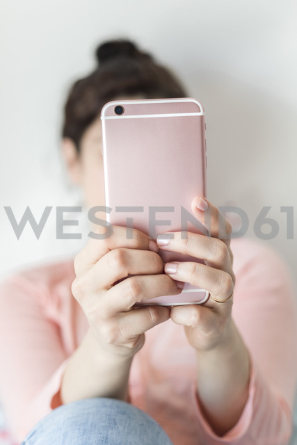 Woman's hands holding pink smartphone, close-up - FLMF00061