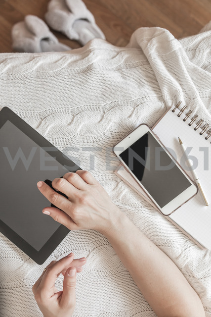 Woman's hand using digital tablet at home, top view - FLMF00067