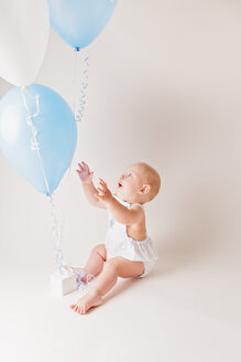 Excited baby boy with balloons and birthday present - NMS00258
