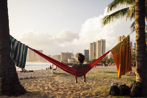 Young woman sitting in hammock at beach, Honolulu, Hawaii Islands, USA - AURF06120