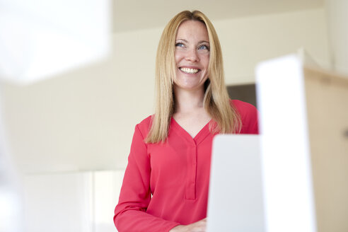 Laughing woman in red blouse, using laptop - PNEF00967