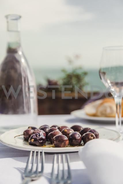Italy, Atrani, black olives on plate - FLMF00076