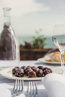 Italy, Atrani, black olives on plate - FLMF00076