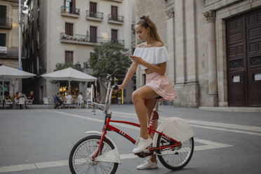 Fashionable young woman exploring Barcelona with a bicycle, using smartphone - AFVF01591