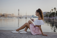 Fashionalble young woman sitting at the harbour of Barcelona, using smartphone - AFVF01609