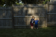 Rear view of brothers peeking through wooden fence while playing at backyard - CAVF48762