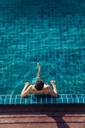 High angle view of shirtless man relaxing in pool at tourist resort - CAVF48774