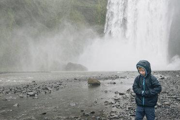 Boy wearing raincoat standing against splashing waterfall - CAVF48792