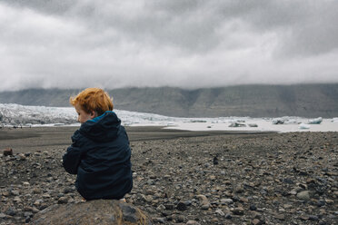 Rear view of boy sitting on rock against cloudy sky during winter - CAVF48798