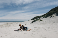 Full length of siblings playing with sand at beach against cloudy sky during sunny day - CAVF48804