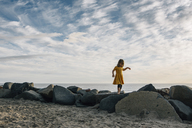 Playful girl walking on rocks at beach against cloudy sky during sunset - CAVF48816