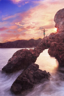 Rear view of shirtless man with arms outstretched standing on rock over sea against sky during sunset - CAVF48894