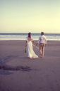 Rear view of newlywed couple holding hands while walking at beach against clear sky during sunset - CAVF48900