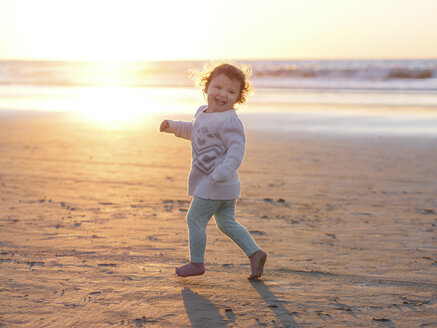 Happy baby girl running at beach against clear sky during sunset - CAVF48945