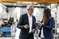 Businessman an woman in high tech enterprise, having a meeting in factory workshop - KNSF04832