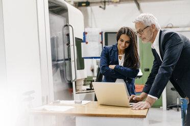 Businessman an woman in high tech enterprise, having a meeting, using laptop - KNSF04844