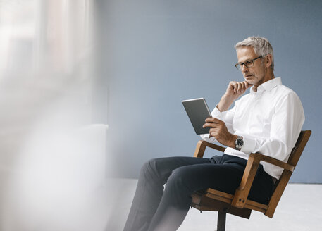 Manager sitting in office, using digital tablet - KNSF04868