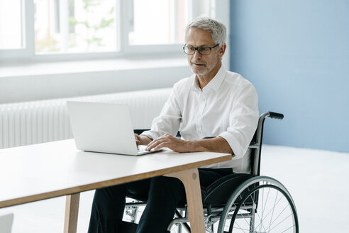 Handicapped manager in a wheelchair, working in office - KNSF04877