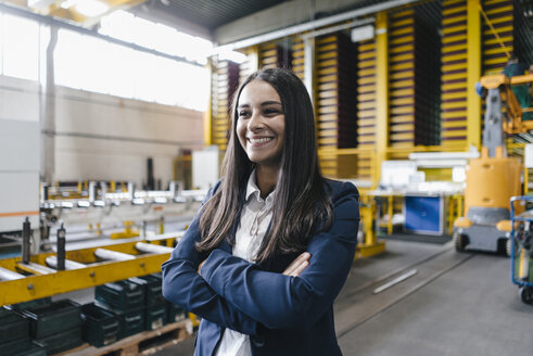 Confident woman standing in logistics center, with arms crossed - KNSF04880