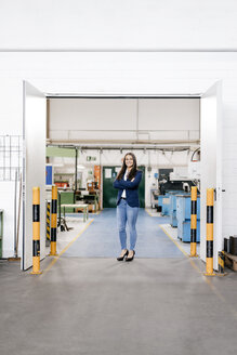 Confident woman working in high tech enterprise, standing in factory workshop with arms crossed - KNSF04883