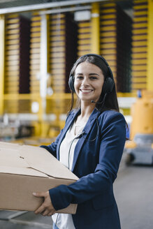 Young woman working at parcel service, carrying parcel in warehouse - KNSF04889