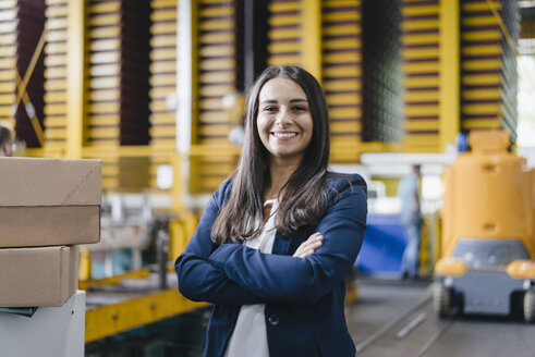 Confident woman standing in logistics center, with arms crossed - KNSF04892