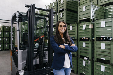 Confident woman working in high tech enterprise, standing in warehouse with arms crossed - KNSF04895
