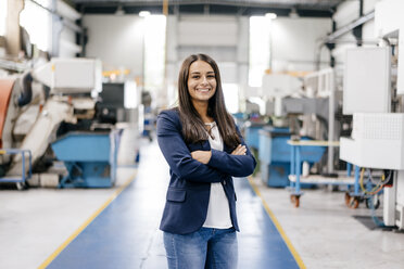 Confident woman working in high tech enterprise, standing in factory workshop with arms crossed - KNSF04898