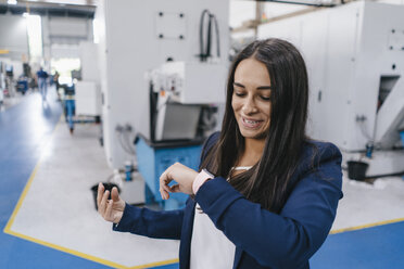 Confident woman working in high tech enterprise, using smartwatch for a call - KNSF04904