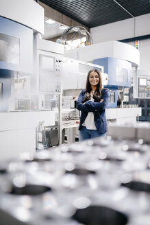 Confident woman working in high tech enterprise, standing in factory workshop with arms crossed - KNSF04910