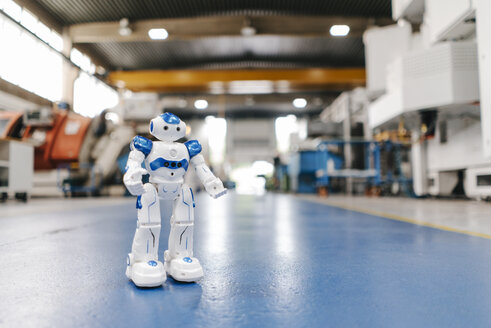 Toy robot standing on floor of factory workshop - KNSF04919