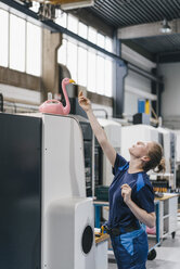 Young woman working as a skilled worker in a high tech company, playing with a pink flamingo - KNSF04955